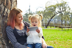 Mother and daughter playing with smartphone Stock Photos