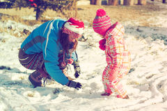 Mother and daughter playing in the snow stock image
