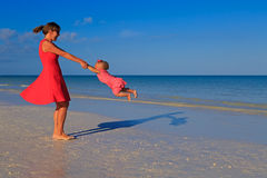 Mother and daughter playing on summer beach Stock Image