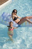 Mother and daughter playing in a swimming pool. With a inflatable bed Royalty Free Stock Photos