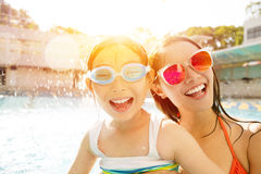 Mother and daughter playing in swimming pool. Happy mother and daughter playing in swimming pool Royalty Free Stock Photo