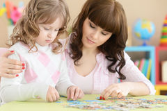 Mother and daughter are playing. At the table Royalty Free Stock Photo