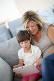 Mother and daughter playing on tablet at home Royalty Free Stock Photos