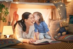 Mother and daughter playing in tent. Family bedtime. Mom and child daughter are reading a book in tent. Pretty young mother and lovely girl having fun in royalty free stock photos