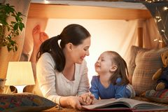 Mother and daughter playing in tent. Family bedtime. Mom and child daughter are reading a book in tent. Pretty young mother and lovely girl having fun in stock photography