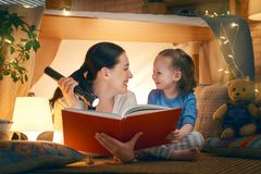 Mother and daughter playing in tent. Family bedtime. Mom and child daughter are reading a book in tent. Pretty young mother and lovely girl having fun in stock images