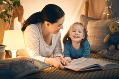 Mother and daughter playing in tent stock image
