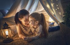 Mother and daughter playing in tent Stock Photography