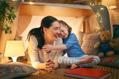 Mother and daughter playing in tent. Happy loving family. Young mother and her daughter girl playing in kids room at the bedtime. Funny mom and lovely child are royalty free stock image