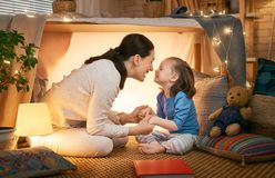 Mother and daughter playing in tent. Happy loving family. Young mother and her daughter girl playing in kids room at the bedtime. Funny mom and lovely child are stock photo