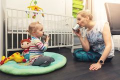 Mother and daughter playing with tin can phone at home royalty free stock photos