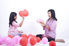 Mother and Daughter playing together. Mother and Daughter playing with balloon isolated on white Stock Photography