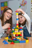 Mother and Daughter Playing Together with colorful building toy blocks stock images