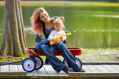 Mother and daughter playing toy guitar in a lake Stock Photos