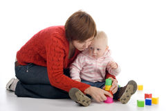 Mother and daughter playing with toys. Little girl with her mother sitting on the floor and play with toys Stock Photos