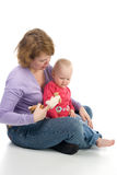 Mother and daughter playing with toys. Mother and daughter sitting on the floor and play with soft toys Royalty Free Stock Photography