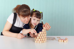 Mother and daughter playing with toys at table Royalty Free Stock Photos