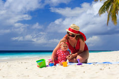 Mother and daughter playing on tropical beach Stock Photography