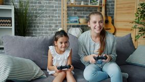 Mother and daughter playing video game at home having fun laughing together