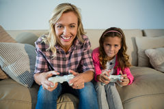 Mother and daughter playing video game in the living room. At home Royalty Free Stock Image