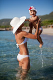 Mother and daughter playing in the water. Stock Images
