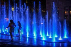 Mother and daughter playing in water fountain at night in Quebec royalty free stock image