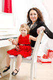 Mother and daughter playing on white piano. In bright room Stock Photos
