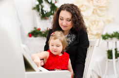 Mother and daughter playing on white piano. In bright room Royalty Free Stock Images