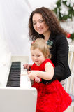 Mother and daughter playing on white piano. In bright room Royalty Free Stock Image
