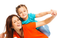 Mother and daughter playing  on white. Smiling mother carrying her funny daughter pick aback like plane Stock Photo