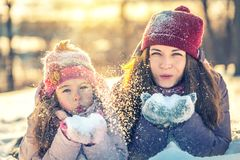Mother and daughter playing in winter park stock photography