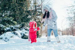Mother and daughter playing on winter park Royalty Free Stock Photography