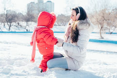 Mother and daughter playing on winter park Royalty Free Stock Image