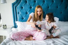 Mother and little daughter plays game console video games on bed at home. Daughter disturb mother. stock photography