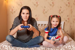 Mother and daughter plays game console. Royalty Free Stock Image
