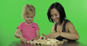 Mother and daughter plays the jenga. Child making a tower from wooden blocks stock video footage