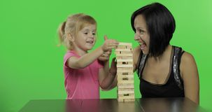 Mother and daughter plays the jenga. Child pulls wooden blocks from tower stock footage