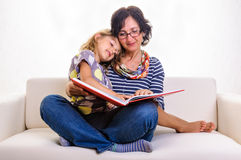 Mother and daughter pointing in big red book Stock Photos