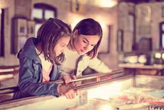 Mother and daughter pointing at sight during. Smiling mother and daughter exploring expositions of previous centuries in museum stock image