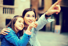 Mother and daughter pointing at sight during Stock Photography