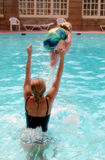 Mother and daughter in pool. Rear view of young mother playing with daughter in swimming pool outdoors stock photo