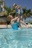 Mother and daughter in pool. Adult woman holding a young girl in a swimming pool, caucasian/white Royalty Free Stock Images