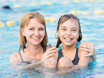 Mother and daughter in pool. Smiling beautiful women and her cute child in the pool. Mother learning to swim her little daughter. Portrait of a happy family Stock Photos