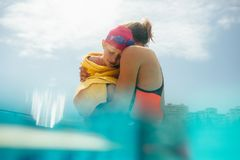 Mother and daughter in the pool. Woman standing in swimming pool carrying her daughter wrapped in towel. Girl feeling cold after swimming in her mother`s arms stock images