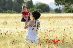 Mother and daughter in a poppy field. A mother with her daughter in a poppy field Royalty Free Stock Photo