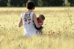 Mother and daughter in a poppy field Royalty Free Stock Photo