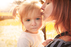 Mother and daughter portrait hug kissing in park Royalty Free Stock Image