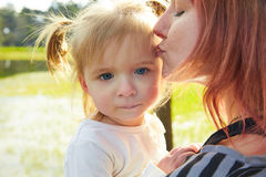 Mother and daughter portrait hug kissing in park Royalty Free Stock Photography