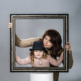 Mother and daughter posing with frame Stock Photo