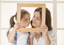 Mother and daughter posing with frame. Young mother and little daughter looking to each other posing with an empty frame Royalty Free Stock Photos